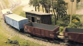 Model railroad track. Train runs through the curve. Rail transportation, entertainment toy industry. Model railroad track. Miniature train runs through the stock footage
