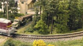 Model railroad track. Train runs through the curve. Rail transportation, entertainment toy industry. Model railroad track. Miniature train runs through the curve stock video