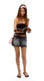 Model reads magazine. Beautiful caucasian brunette model in jeans skirt walks and reads magazine Stock Photo