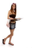 Model reads magazine. Beautiful caucasian brunette model in jeans skirt walks and reads magazine Royalty Free Stock Images