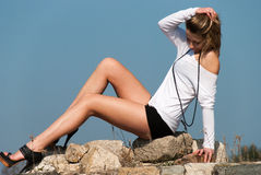 Model reclining on rocks, shows off her long legs Stock Images