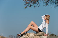Model reclining on rocks, shows off her long legs Stock Photography