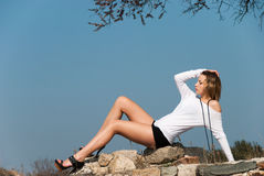 Model reclining on rocks, shows off her long legs Stock Photos