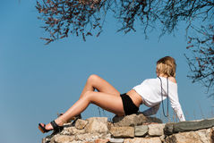 Model reclining on rocks, shows off her long legs Royalty Free Stock Photo