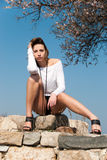 Model reclining on rocks, shows off her long legs Royalty Free Stock Images