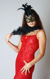 Model in red at a carnival. Model in red lacy dress with face under a mask befeathered, black plume in her hand Royalty Free Stock Photography