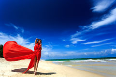 Model in red dress posing on beach Royalty Free Stock Image