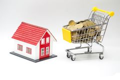 Model red house and coin in shopping cart concept for mortgage saving on white background.  royalty free stock images
