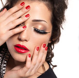 Model with red nails, lips and creative eye makeup Royalty Free Stock Images