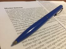 Model release form. And pen on wooden table Royalty Free Stock Images