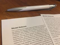Model release form. And pen on wooden table Stock Photography