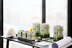 Model of residential quarter. And hardhats on table in office Royalty Free Stock Photos