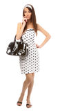 Model in retro clothes. Beautiful model in polka-dot dress with black bag tries to recall something Royalty Free Stock Photos