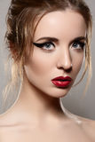 Model with retro make-up, vintage red lips & eyeliner. Portrait of fashion model face with glamour lips make-up, eyeliner, clean skin and shiny retro hairstyle Stock Image