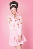 Model In Retro Style Over Pink. Sixties fashion woman in soft pink outfit with retro hairstyle and makeup posing over pink background Stock Photo