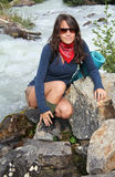 Model  on the rocks of a mountain stream Stock Photo