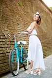 Model in romantic image poses near vintage bicycle, brick wall royalty free stock photography