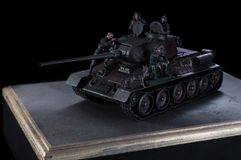 Model of the Russian tank T-34 fighting vehicle, with three soldiers nearby. Black background stock photo