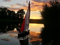Model sailboat in front of sunset Royalty Free Stock Photo