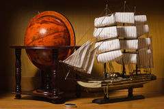Model sailing ship and old globe. On a table stock photography