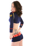 Model looking over her shoulder. Model in skimpy sailor outfit with gold stripes and tattoo looking over her shoulder on white background stock photos