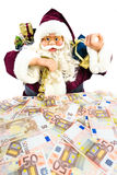 Model of Santa Claus with gifts and euro money. Model of Santa Claus with presents and euro notes isolated on white background Stock Image