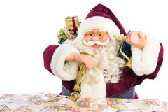 Model of Santa Claus with presents and euro money. Model of Santa Claus with gifts and euro notes isolated on white background Stock Photography