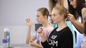In model school women are making bundle. Young and beautiful females are standing around girls making hair done in classical ballet hairstyle. One is holding stock video footage