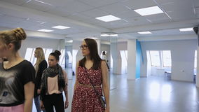 In model school women are preparing for defile. Under teacher control young and beautiful females are walking up and down getting ready for fashion show stock footage