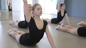 In model school young and beautiful women are lying on the floor. Doing stretching exercises. They are lifting their hands in turn holding hands back together stock video