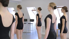 In model school young and beautiful women are preparing for dance class. Or ballet lesson. Females are standing in front of the mirror trying to hold the pose stock video