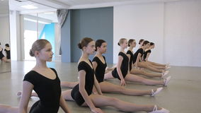 In model school young and beautiful women are stretching sitting on twine. In turn. Females are doing physical exercises being in dance class or on ballet stock footage