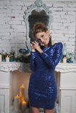 Model in short blue dress near christmas decorated commode Royalty Free Stock Image
