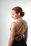 Model in short dress with nude back, half-turn. Young woman stands half-turn in black dress with naked back on light background. There are a lot of strings on Royalty Free Stock Photos