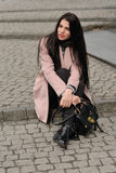 Model shows autumn clothes sitting on the sidewalk Stock Photo