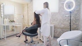 Model siedzi w krześle makijażu artysta stylista szczotkuje jej włosy, twirls kędziory na forceps A zbiory