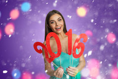 Model with sign of New Year 2016. Smiling young woman holding decorative sign of New Year 2016 Stock Image