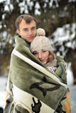 Happy young family. Lucky beloved couple hug each other in the cold weather in winter forest.December.Cheerful good mood. Stock Images