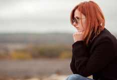 Beautiful red-haired unhappy depressed girl with glasses of something thought. The red-haired girl sits somewhere in mountains and thinks much. Thinker. In sun Royalty Free Stock Photos