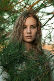 Very beautiful girl with green eyes stand in green fir-tree Stock Photo