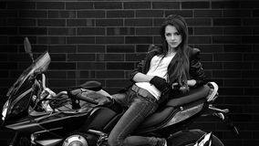 Seductive girl sits on bike on black background with leather jacket Royalty Free Stock Photo
