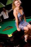 Model sitting on billiards table Stock Photo