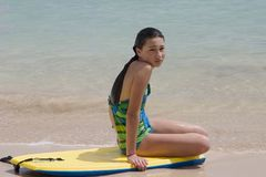 Model sitting on a board at the ocean. Young model sitting on a boogy board in the ocean Stock Images