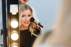 Model sitting in front of mirror while applying. Makeup finishing. Female young model sits in front of lighted mirror while makeup artist works with her royalty free stock photography