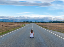 Model sitting on long straight road with mountains in distance. Beautiful clouds, blue sky, in a very rural/wilderness area of New Zealand Royalty Free Stock Images