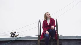 Model sitting on roof in winter. Media. Attractive young woman model posing sitting on roof with ladder on background of. Model sitting on roof in winter. Media stock video