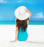Model sitting in swimsuit with hat. Picture of model posing in swimsuit with hat on the beach Royalty Free Stock Image