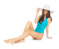 Model sitting in swimsuit with hat Stock Images