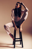 Model sitting in top and striped pants Stock Photography