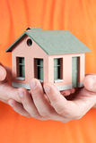 Model of the small house in human hands. Royalty Free Stock Image